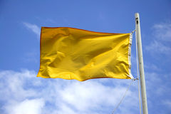 Yellow Caution Flag. Yellow flag with blue cloudy sky Stock Photography