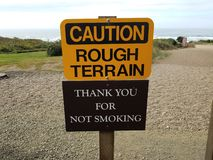 Yellow caution rough terrain thank you for not smoking signs