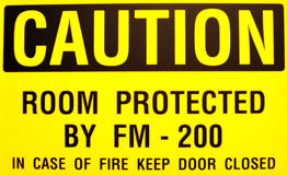 Yellow Caution Sign. Black and yellow caution sign warning to keep door closed in case of fire Stock Photo