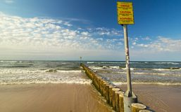 Yellow caution sign, Baltic Sea Royalty Free Stock Photography