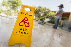Yellow caution sign and blur of man doing floor polishing Stock Photography