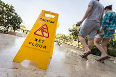 Yellow caution sign and blur of paeple walking on the walkway Stock Photography