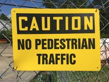 Yellow caution sign at construction site. Yellow caution no pedestrian traffic sign at construction site on a chainlink fence with construction materials in the royalty free stock photography