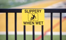 Yellow caution sign warns surface is `Slippery When Wet`. Yellow `Slippery When Wet` warning sign on hand rail to avoid dangerous situation Stock Images
