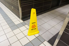 Yellow caution slippery wet floor sign labeled in English and Fr Stock Images
