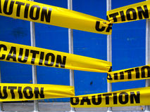 Yellow caution tape. On a metal barrier royalty free stock images