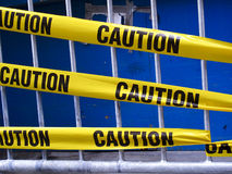 Yellow caution tape. On a metal barrier Stock Image