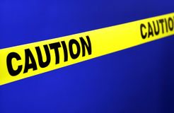 Yellow caution tape. Large yellow caution tape stretched across blue background stock photography