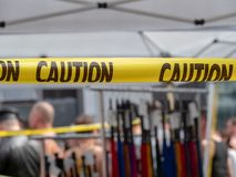 Yellow caution tape hanging in front of BDSM store with whips. Displayed royalty free stock images