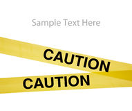 Yellow caution tape on white with copy space. Yellow caution tape on a white background with copy space royalty free stock photography