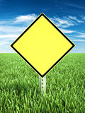 Yellow caution themed sign placed in a field of grass with room for text or copy space. Royalty Free Stock Image