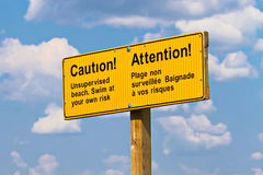 A yellow caution unsupervised beach sign in french and english stock images