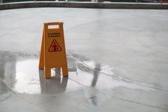 Yellow Caution wet floor cleaning in progress sign on wet floor. Yellow Caution wet floor sign on wet floor Royalty Free Stock Photos