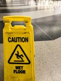 Yellow Caution wet floor sign. At an airport Royalty Free Stock Photography