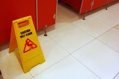 Yellow Caution wet floor sign in public toilet restroom. Yellow Caution wet floor sign in public toilet Stock Images