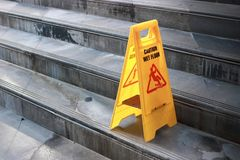Yellow caution wet floor sign at staircase of outdoor city. Yellow caution wet floor sign at staircase of outdoor city Stock Image