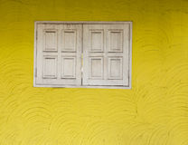 Yellow cement wall texture and old white wooden window Royalty Free Stock Photo