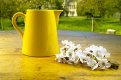 Yellow ceramic can and flowers on old wooden table Stock Photos