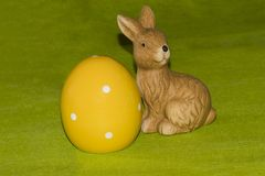 A yellow easter egg and an Easter bunny in front of a green background. A yellow ceramic easter egg and an Easter bunny in front of a green background stock photo
