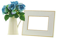 Yellow ceramic jug vase next to blank beige wooden picture frame Stock Photography