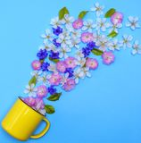 Yellow ceramic mug and buds of flowers. Scattered on a blue background Royalty Free Stock Photography