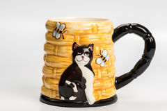 Yellow ceramic mug with cat  on white. Background Royalty Free Stock Photos