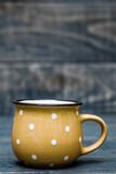 Yellow Ceramic Mug with White Dots on Blue Wooden Background Stock Photo