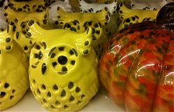 Yellow ceramic owls and Orange Glass Pumpkins Display. Ceramic yellow and white owls, and orange glass pumpkins in display. For use in Halloween announcements Royalty Free Stock Photography