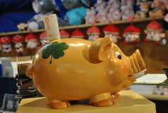 Yellow ceramic piggy bank. With  10 Euro banknote on the shelf in the shop Stock Photo