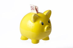 Yellow ceramic piggy bank with one bank note. Yellow ceramic piggy bank isolated on white background Royalty Free Stock Photos