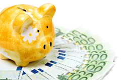 Yellow ceramic piggy bank on a pile of banknotes Royalty Free Stock Images