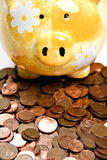 Yellow ceramic piggy bank on a pile of cents Stock Photo