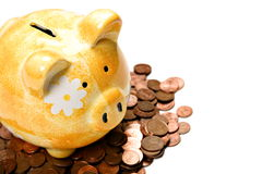 Yellow ceramic piggy bank on a pile of cents Royalty Free Stock Photography