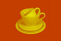 Yellow ceramic tea cups with saucers on orange color background Royalty Free Stock Photo