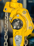 Yellow chain hoist. Chain hoist for lifting with a blurred background stock illustration