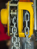 Yellow chain hoist. Chain hoist for lifting with a blurred background Royalty Free Stock Photos