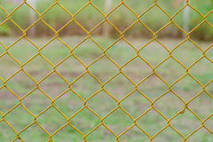 Yellow Chain Link Fence. With natural green background royalty free stock images
