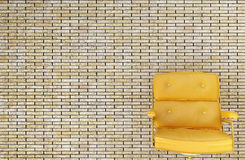 Yellow chair. Against a brick wall Stock Photos