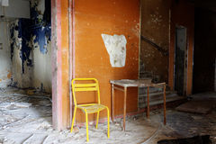 Yellow chair and brocken table. A yellow chair and a table in a orange corridor Royalty Free Stock Photos