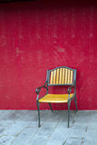 Yellow chair. Empty yellow chair next to red wall Stock Photos