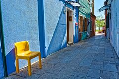 Yellow chair in front of blue wall in an alley in Burano stock images