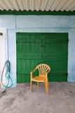 Yellow chair in front of a green door Stock Photo