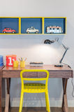 Yellow chair and wooden desk with modern black lamp Royalty Free Stock Photography