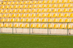 Yellow chairs on the green soccer field Royalty Free Stock Photo