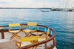 Yellow Chairs on a Sailboat Deck. With Boats in the Background Royalty Free Stock Images