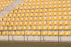 Yellow chairs on the soccer field. Many yellow empty chairs on the soccer field Stock Photos