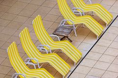 Yellow chaise lounges. A row of yellow chaise lounges or reclining chairs on a patio royalty free stock photography