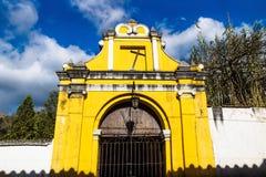 Yellow chapel church fasade under blue cloud sky, Antigua, Guatemala. Yellow chapel church fasade with crooked cross under blue cloud sky, Antigua, Guatemala royalty free stock photo
