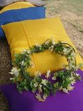 Yellow chaplet on colourful cushion. Chaplet and purple cushion on lifely morning on green lawn Stock Photography