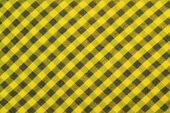 Yellow checked tablecloth background. Yellow gingham or checked fabric tablecloth texture background Stock Image